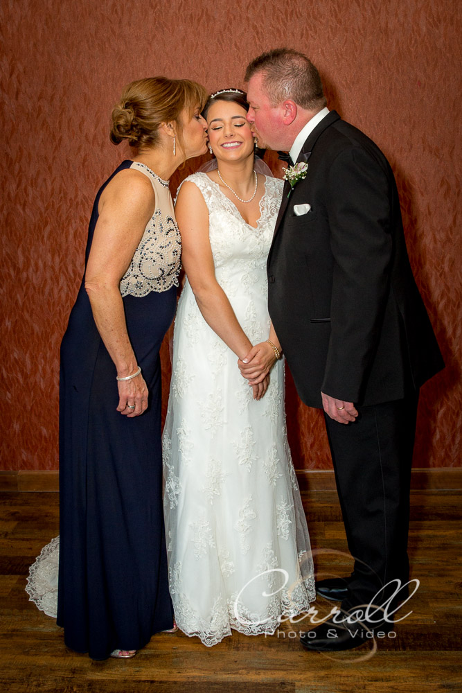 Brides mom and Dad giving bride kisses on her cheeks at wedding at The Vineyards at Pine Lake - Columbiana Wedding Photography by Youngstown Wedding Photographers Carroll Photo and Video