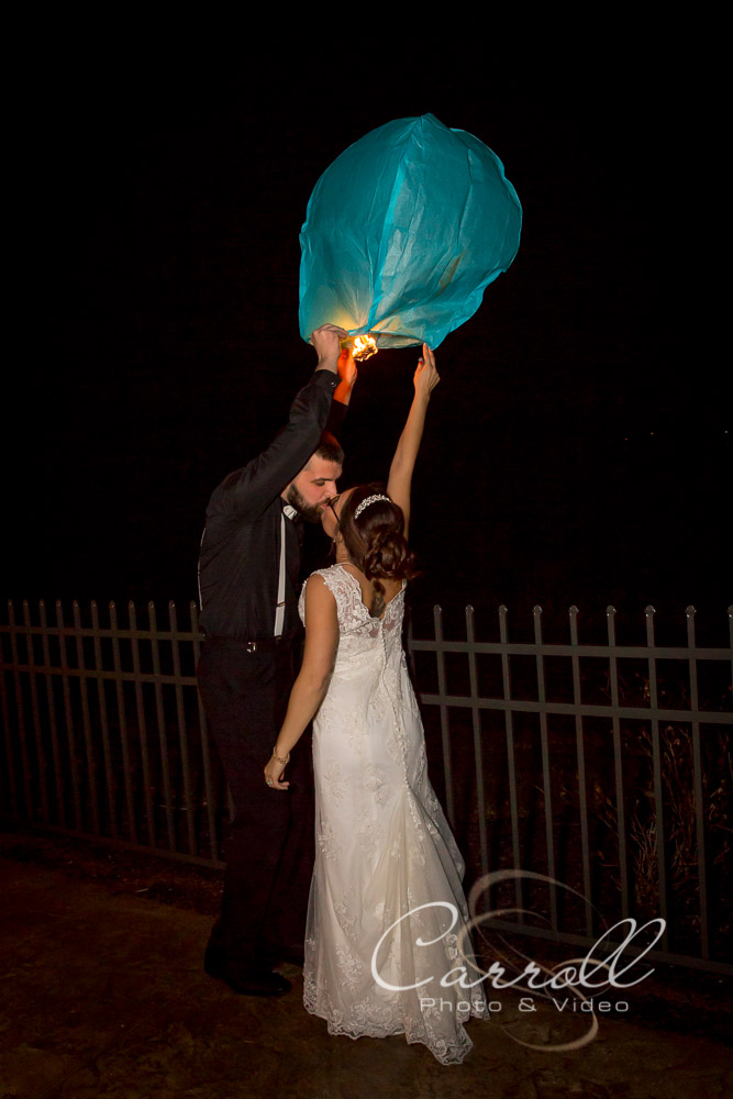 Bride and Groom kissing and sending off a Sky lantern at end of wedding reception at The Vineyards at Pine Lake - Columbiana Wedding Photography by Youngstown Wedding Photographers Carroll Photo and Video